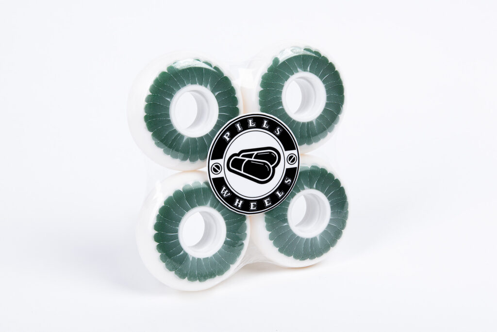 White Polyurethane 64 mm Wheels with White Cores, Tinted Green Flower, Grey Linocut Outlines Design and Black and White Pills Wheels Logo